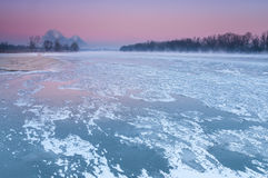 Chaminés de fumo sobre um rio enevoado e congelando-se durante o crepúsculo Imagem de Stock Royalty Free