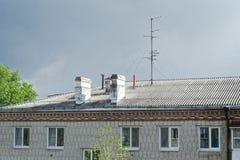 Chaminés e antena da televisão no telhado da casa de apartamento contra o céu nebuloso fotos de stock