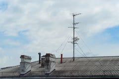 Chaminés e antena no telhado de uma casa de apartamento contra o céu nebuloso azul fotos de stock
