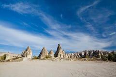 Chaminés e lotes feericamente do céu azul, Cappadocia Imagem de Stock