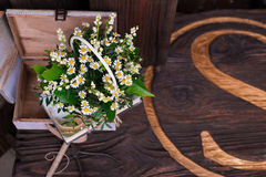 Chamomile decor composition with books and box on the brown wood table Royalty Free Stock Photos