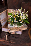 Chamomile decor composition with books and box on. The old brown wood table. Selective focus with bokeh Royalty Free Stock Photo