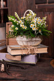 Chamomile decor composition with books and box on. The old brown wood table. Selective focus with bokeh Royalty Free Stock Images