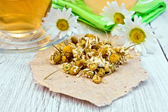 Chamomile dried on paper with glass cup Stock Images