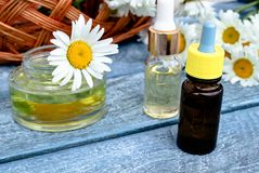 Chamomile essential oil in a glass jar and a bottle near chamomile stock photography