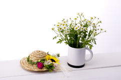 Chamomile flower. In cup and mini straw hat on table Stock Photo
