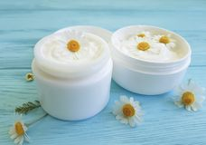 Chamomile flower, cosmetic ointment protection treatment sample skin cream product on a blue wooden background stock images