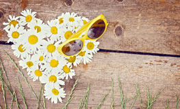 Chamomile flowers as a shape of heart and sunglasses lie on wood Stock Photo