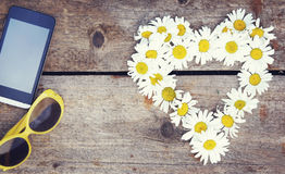 Chamomile flowers as a shape of heart, sunglasses and smartphone Stock Photography