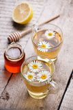 Chamomile flowers and chamomile tea. Chamomile tea in cup with flowers, honey and lemon, close-up. Seasonal treatment, alternative royalty free stock image
