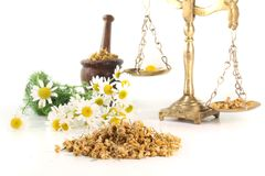 Chamomile flowers with mortar and scales Royalty Free Stock Photo