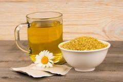 Chamomile gorąca herbata i suszy rośliny na nieociosanym drewnianym stole obraz royalty free