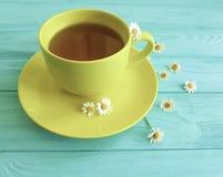 Chamomile kwiat, filiżanka ranku herbata na błękitnym drewnianym tle świeżość obrazy royalty free