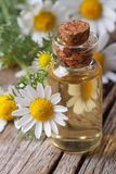 Chamomile oil in a glass bottle macro vertical Royalty Free Stock Images
