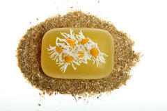 Chamomile soap. Yellow soap and dried flowers of chamomile on a white background Royalty Free Stock Photo