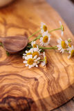 Chamomile tea with chamomile daisy flowers. In a hot white cup on a wooden rustic cutting board and a spoon. This home remedy is known to help sleep and aid a royalty free stock photos