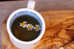 Chamomile tea with chamomile daisy flowers. In a hot white cup on a wooden rustic cutting board and a spoon. This home remedy is known to help sleep and aid a royalty free stock image