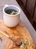 Chamomile tea with chamomile daisy flowers. In a hot white cup on a wooden rustic cutting board and a spoon. This home remedy is known to help sleep and aid a royalty free stock photography