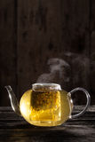 Chamomile Tea in a Clear Teapot. Ready and Hot Chamomile Tea in a Clear teapot on a Wood Table Stock Photos