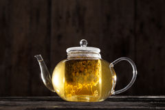 Chamomile Tea in a Clear Teapot. Ready and Hot Chamomile Tea in a Clear teapot on a Wood Table Royalty Free Stock Photo