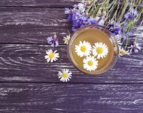 Chamomile tea, cornflower rustic floral morning retro on a vintage wooden background. Chamomile tea cornflower on a wooden background retro vintage rustic Stock Image