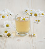 Chamomile tea and some chamomile flowers. Chamomile tea, some chamomile flowers on a wooden table Royalty Free Stock Images