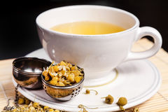 Chamomile tea in the white glass with opened tea strainer Royalty Free Stock Photo