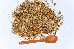 Chamomile tea and a wooden spoon on a white surface Stock Photos