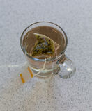 Chamomile teabag in glass mug on table Stock Photography