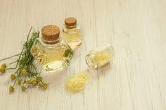 Chamomile wodny hydrolate w szklanych butelkach, żółtej kąpielowej soli i świeżych kwiatach na białym drewnianym stołowym tle, obraz royalty free