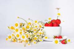 Chamomiles and strawberries in the cup Royalty Free Stock Photos