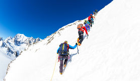 CHAMONIX, FRANCE - MARCH 19, 2016: a group of mountaineer climb a snowy peak. In background the glaciers and the summit of Mont Bl Royalty Free Stock Photography