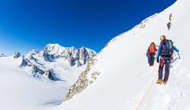 CHAMONIX, FRANCIA - 19 DE MARZO DE 2016: un grupo de subida del montañés un pico nevoso En fondo los glaciares y la cumbre de Mon Fotos de archivo