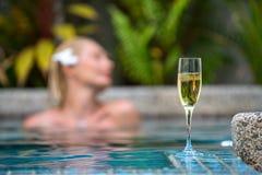 Champán cerca de la piscina en un fondo de una mujer hermosa Fotos de archivo