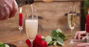 Champán de colada en un vidrio en una tabla con las velas y las rosas rojas almacen de video