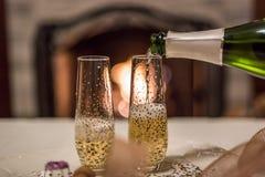 champán de colada de la botella en el vidrio delante de la chimenea foto de archivo