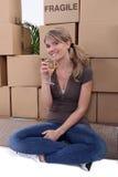 Champán de consumición de la mujer cerca de las cajas de embalaje Imagen de archivo libre de regalías