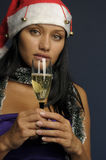 Champán de consumición de la mujer hermosa en la Navidad Imagenes de archivo