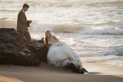 Champán de consumición de los pares nupciales hermosos jovenes en la playa Fotografía de archivo libre de regalías