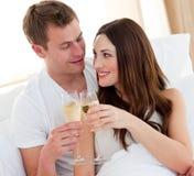 Champán de consumición de los pares románticos que miente en cama Fotografía de archivo libre de regalías
