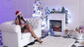 Champán de consumición de la muchacha atractiva cerca del árbol de navidad almacen de metraje de vídeo