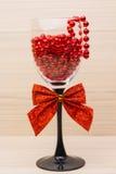 Champán de la Navidad con las gotas, las decoraciones del árbol y el lazo rojos Foco selectivo en la tabla de madera Imagen de archivo