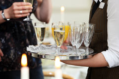 Champán de la porción del camarero y zumo de naranja Imagenes de archivo
