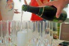 Champán de la porción en por de los vidrios de consumición un partido Foto de archivo libre de regalías
