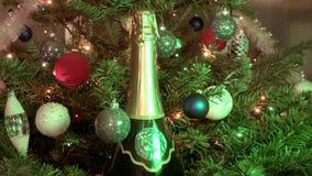 Champán del vino espumoso entre el abeto de la Navidad adornado por las bolas del ` s del Año Nuevo metrajes