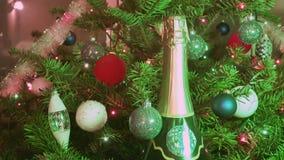 Champán del vino espumoso entre el abeto de la Navidad adornado por las bolas del ` s del Año Nuevo almacen de video