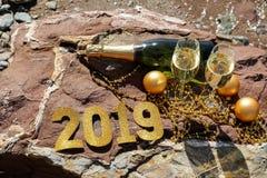 Champán en una playa pedregosa por el mar, Año Nuevo celebra concepto de la preparación Fotografía de archivo