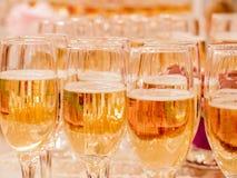 Champán en vidrios en las tablas de banquete Fotos de archivo