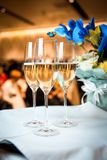 Champán en vidrios en la tabla con las flores Imagen de archivo