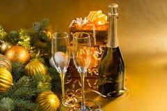 Champán festivo y regalos con las decoraciones del oro Fotos de archivo